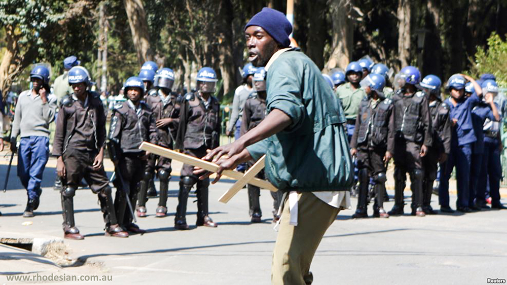 Protester is confroneted in Harare in front of riot police
